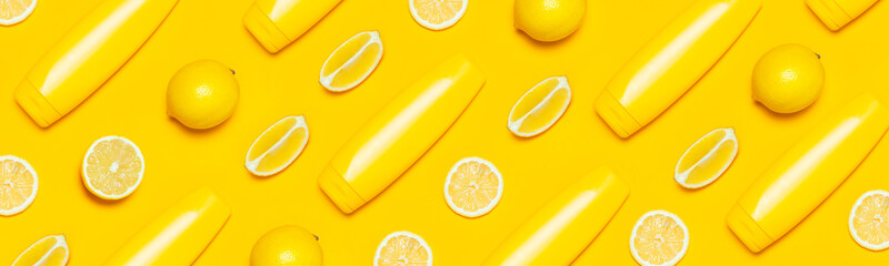 Creative summer concept. Yellow Cosmetic bottle containers, fresh citrus lemon on yellow background top view flat lay copy space. Blank label for branding mock-up Natural beauty product sunscreen.