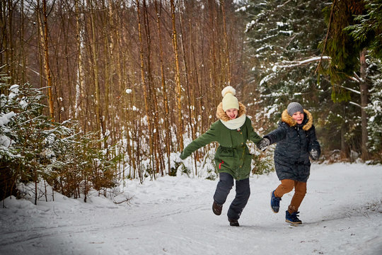 Children boy and girl runing in snow forest in a winter day. Teenagers having trip and rest in weekend outdoor
