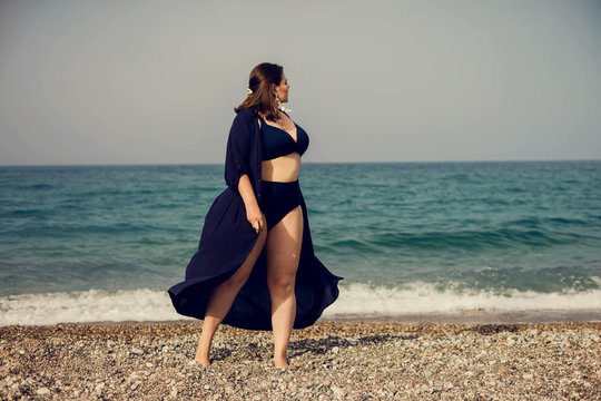 Attractive busty curvy woman in a blue swimsuit resting on the beach. Stylish accessories, fringe, fashion for plus size, beautuful sea. Bodypositive, natural authentic beauty, resort, summer vacation