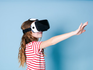 smiling positive girl wearing virtual reality glasses goggles headset, vr box. connection, modern, new generation, concept. girl trying to touch objects in virtual reality, studio shot on blue backgro
