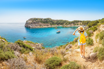 Rear view of a lonely girl with a yellow backpack admiring a beautiful azure Bay in a tropical resort Fototapete