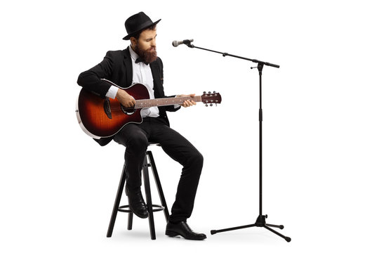 Man playing an acoustic guitar with a microphone in front of him