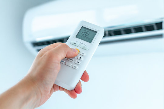 Air conditioner temperature adjustment with remote controller in room at home.