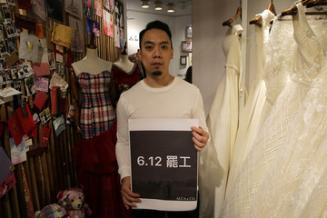 """Alan Li poses with a sign reading """"June 12 Strike"""" inside his clothing store Alca&Co as he decided to close the business for a day in protest against the proposed extradition bill in Hong Kong"""