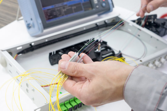 Splicing the fiber optic cable on spice tray with worker hands
