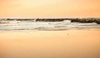 sunset on the beach background with rocks and the orange color of the sky reflected in the sand