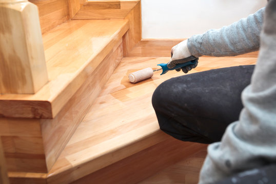 The painter  paints a varnish wooden board by roller