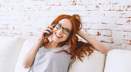 portrait einer jungen rothaarigen frau zu hause beim telefonieren