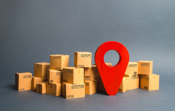 Lots of cardboard boxes and a red position pin. Locating packages and goods. Algorithm for constructing a minimum route for the delivery of orders. Logistics transportation, storage warehouse.