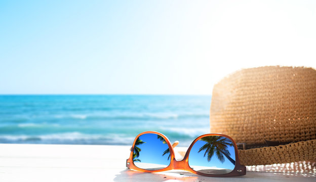 summer tropical beach background; glasses and palm tree reflex