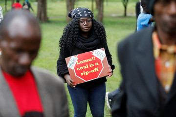 A Greenpeace environmental activist holds a sign against the construction of a coal fired electricity plant in Lamu on Kenya's coast, during a protest in Nairobi