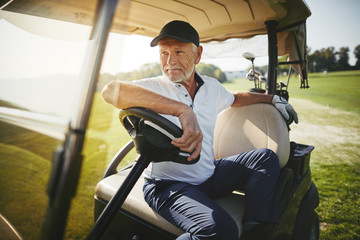 Senior man sitting in his golf cart on a fairway