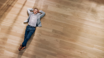 Young Man is Lying on a Wooden Flooring in an Apartment. He's Wearing a Jacket and White Shirt. Cozy Living Room with Modern Minimalistic Interior and Wooden Parquet. Top View Camera Shot.