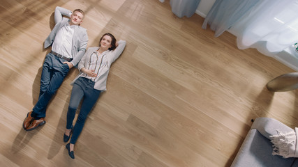 Young Couple are Lying on a Wooden Flooring in an Apartment. They are Happy, Smile and Laugh. Cozy Living Room with Modern Interior, Grey Sofa and Wooden Parquet. Top View Camera Shot.