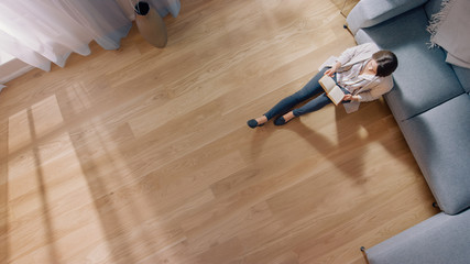 Young Woman is Sitting on a Floor and Reading a Book. Cozy Living Room with Modern Interior, Grey Sofa and Wooden Flooring. Top View Camera Shot.