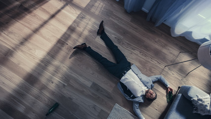 Poor Depressed Drunk Young Man is Crawling Towards a Sofa in an Apartment with Wooden Flooring. He's Holding a Bottle of Beer and Tries to Drink the Leftovers. Dramatic Top View Camera Shot.