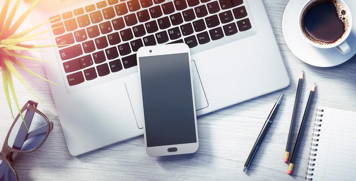 Smartphone und Laptop auf hellem Schreibtisch im Sonnenlich