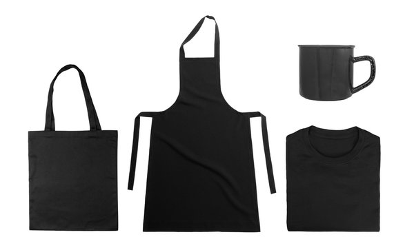 Collection of black objects isolated on white background. Black cotton bag, black folded t-shirt, kitchen apron, metal mug. Flat lay. Top view