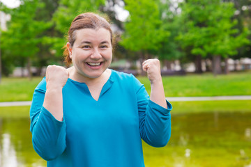 Happy excited plus sized woman celebrating success. Cheerful Caucasian lady making winner gesture with both hands and smiling at camera. Winning concept