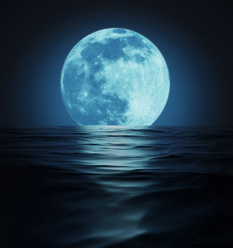 Big Blue Moon Reflected in Dark Wavy Water Surface