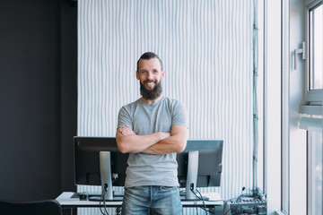 IT administration. Portrait of successful software engineer standing at workplace with arms folded, smiling. Copy space.