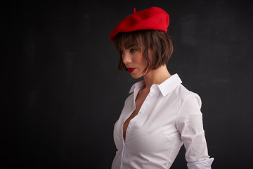 Portrait of attractive young woman wearing red beret and white shirt