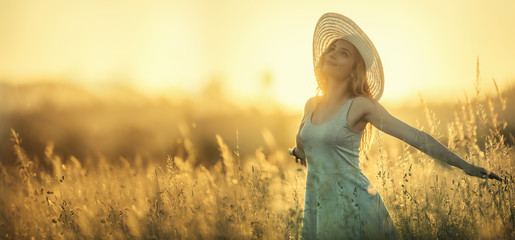 Happy young woman on the sunset or sunrise in summer nature with open hands Wall mural