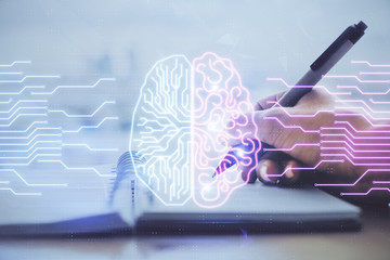Double exposure of writing hand on background with brain hologram. Concept of learning.