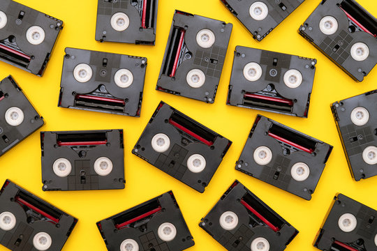 Vintage mini DV cassette tapes used for filming back in a day. Random pattern made of plastic video tapes on yellow background