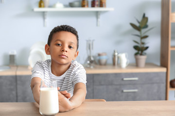 Cute African-American boy refusing to drink milk at table