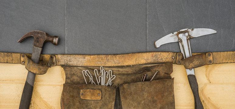 Dachdecker alte Gürteltasche mit authentischem Werkzeug Einschlaghaken und Nägel auf Schiefer