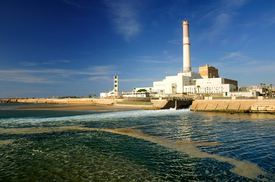 View to massive power station in old Tel Aviv port with sea water at the foreground.