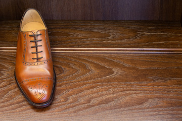 Brown full grain leather shoe on wooden display in men shoes boutique store.