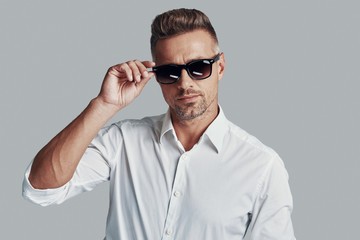 In his own style. Handsome young man looking at camera and adjusting sunglasses while standing against grey background Wall mural