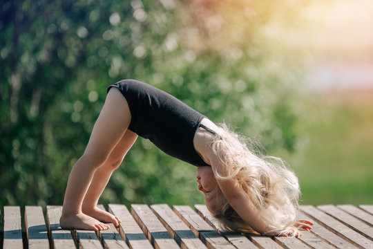 little girl doing yoga in the Park on a Sunny summer day. The concept of health and happiness