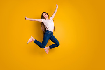 Full length side profile body size photo beautiful amazing she her stylish lady very long hair flight jump high spread hands arms wear casual jeans denim pink shoes t-shirt isolated yellow background