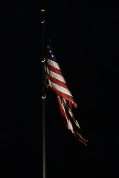 bright american flag flapping and flying high in night