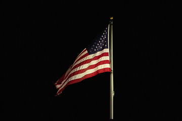 american flag flapping and flying high in night darkened sky