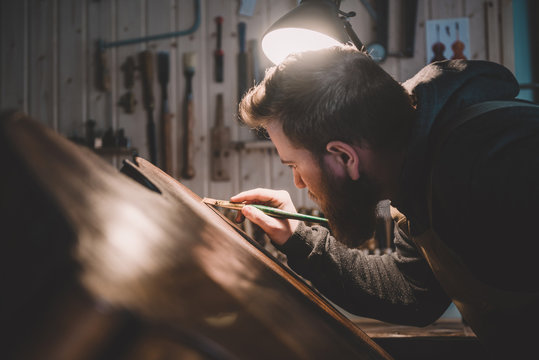 Young luthier working in his workshop, building a double bass