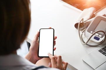 Top view  doctor using smartphone with empty screen display.