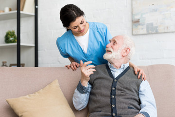 Doctor standing behind senior man, talking to happy patient