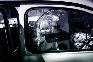old doll looks out of the car window, background for halloween, scary picture
