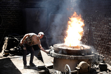 An Iraqi worker checks the oven of cast iron at an iron casting factory in Baghdad