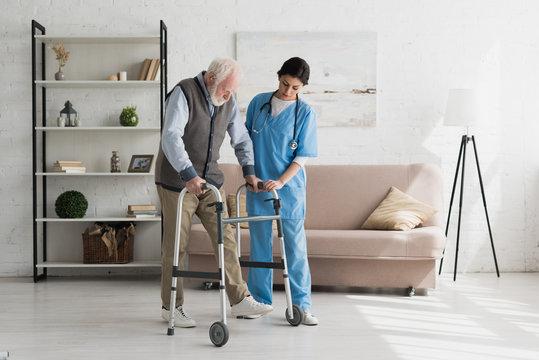 Nurse helping to senior man walking at home, recovering after injury