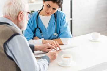 Cropped view of nurse looking at senior man with newspaper in hands