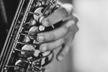 Black and white arty closeup picture of hands of a man playing saxophone
