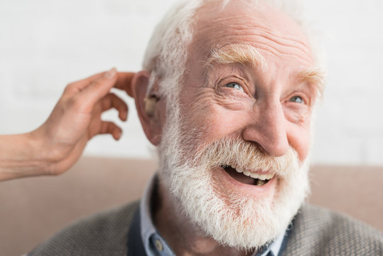Woman hand helping grey haired man, wearing hearing aid
