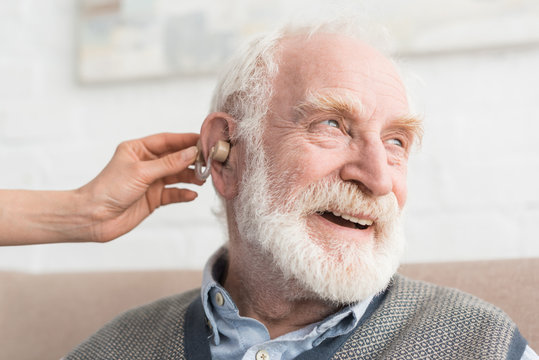 Happy grey haired man with hearing aid, and looking away
