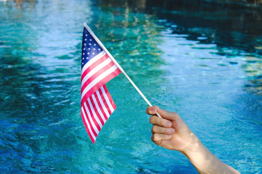 Hand waving American flag with blue pool water in background.  Fourth of July holiday celebration concept.