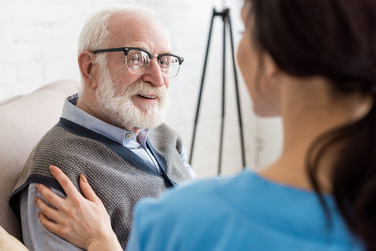 Selective focus of cheerful and grey haired man looking at nurse